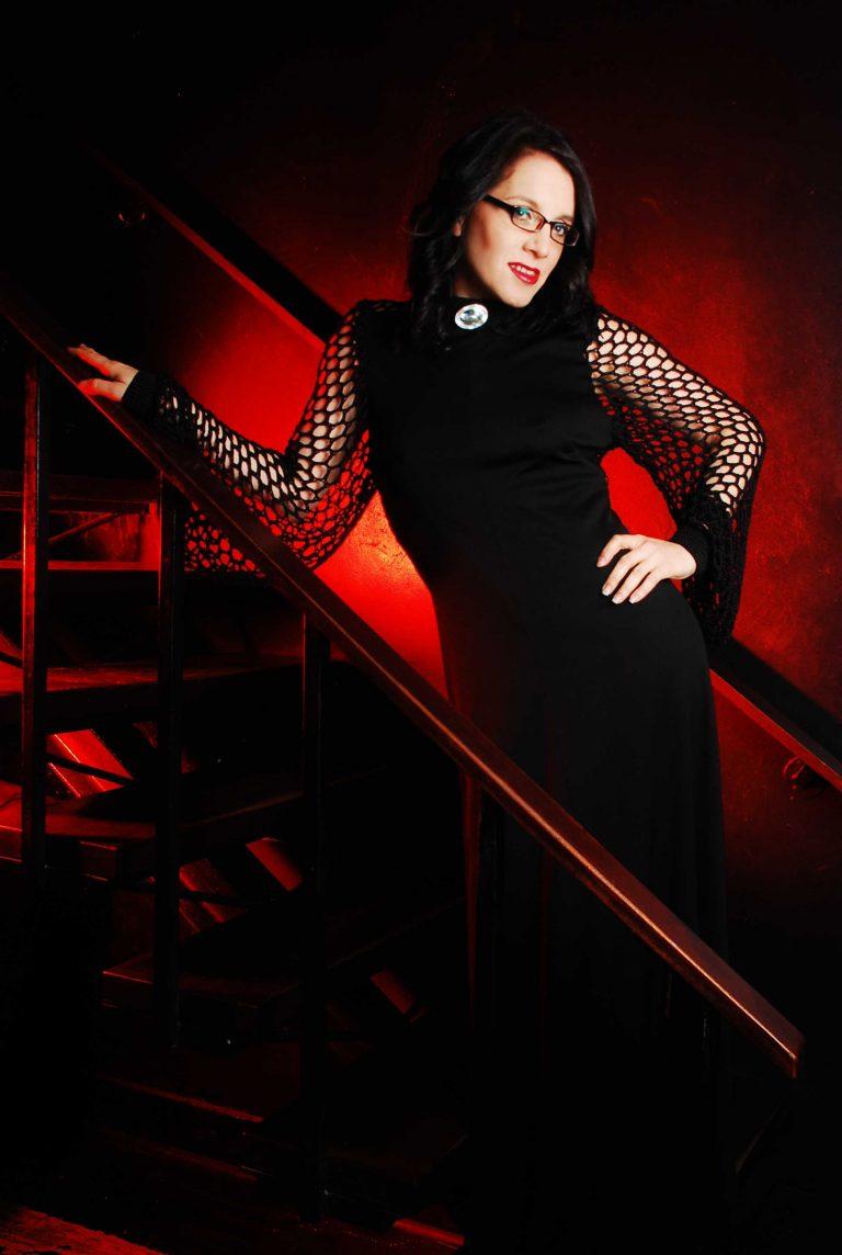 Event Companion Debra wearing floor-length black dress with net-like sleeves